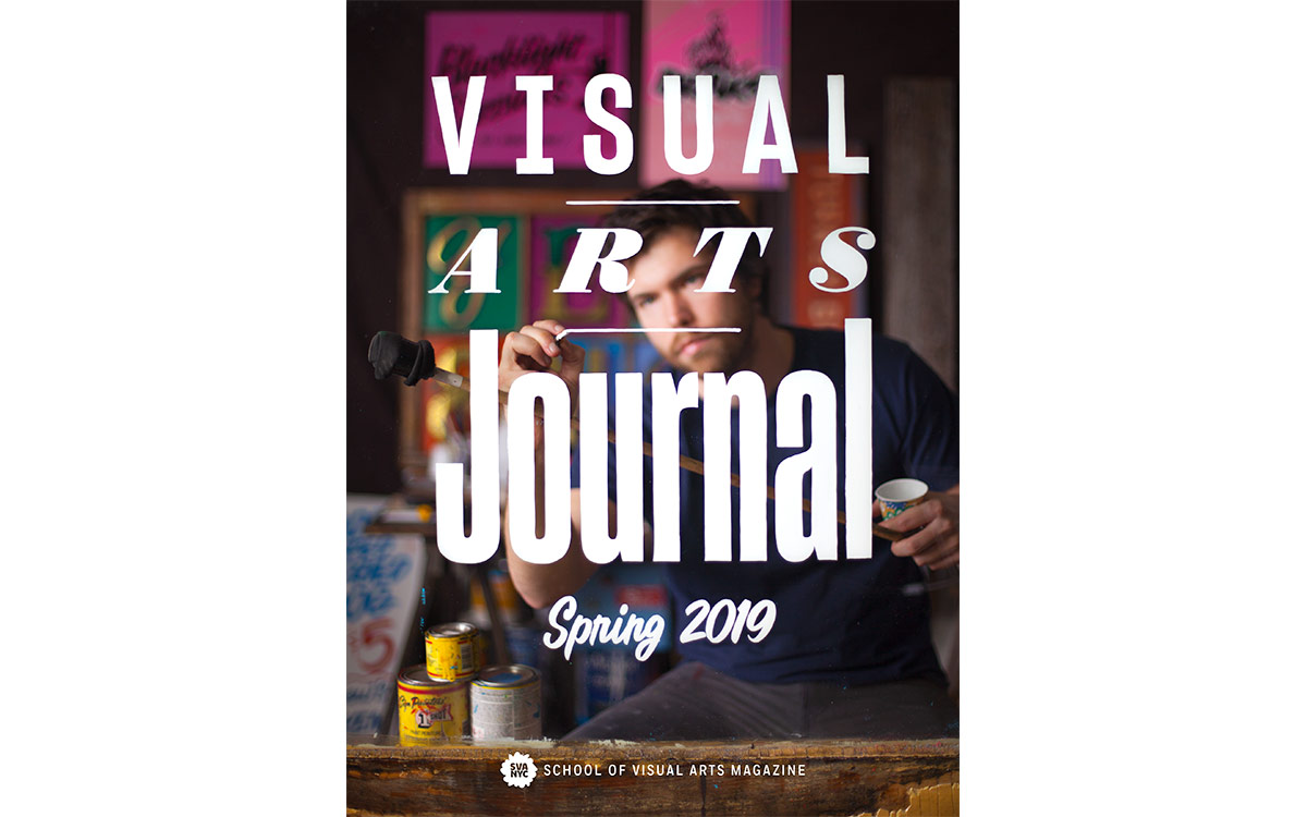 """<p """"="""""""">A man puts the finishing touches on a glass pane painted with the words """"Visual Arts Journal Spring 2019."""" <strong><br></strong>"""