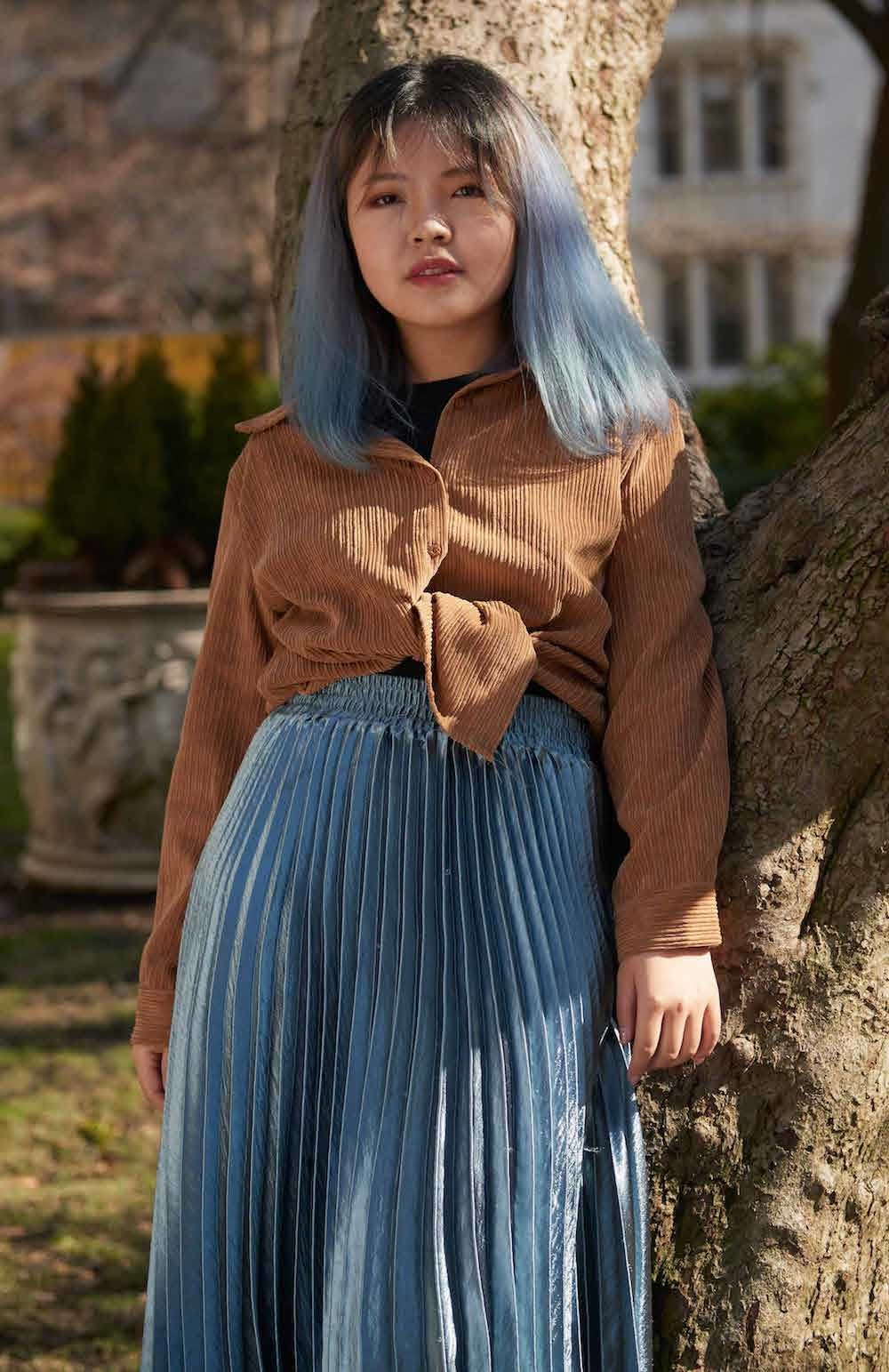 A young woman with dyed blue hair, corduroy shirt and pleated blue skirt.