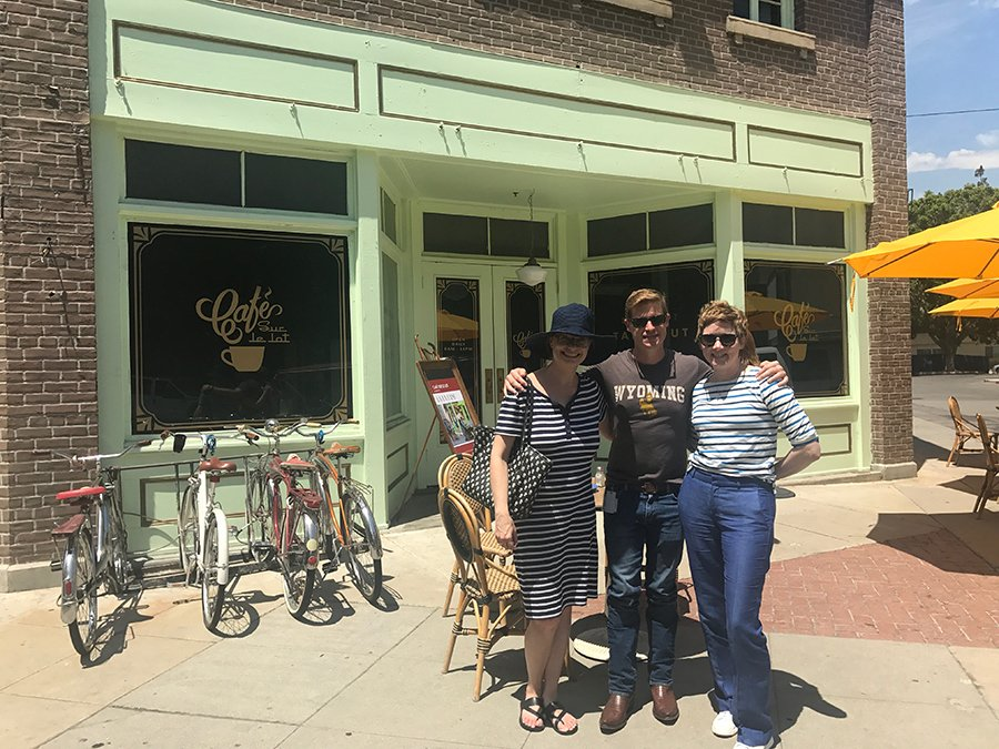 There are 2 women and one male posing for a picture in front of Cafe Sue le lot.