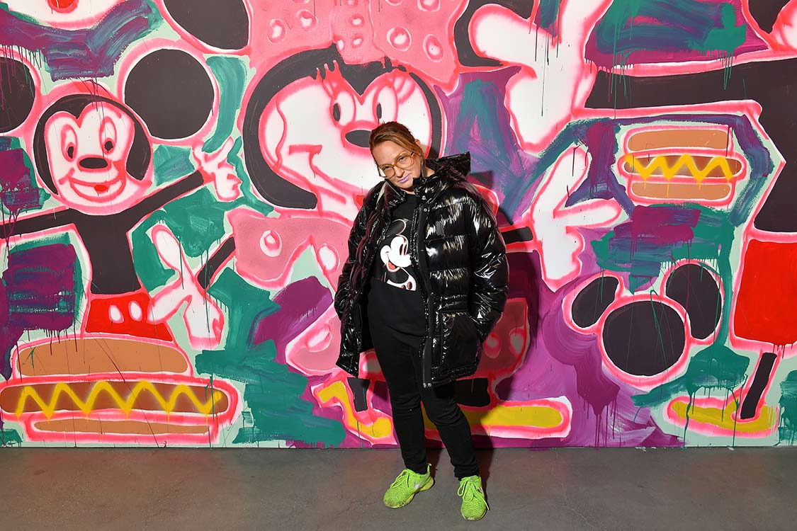 """<p """"="""""""">A woman wearing a Mickey Mouse shirt and black coat stands in front of her large spray paint and acrylic mural, which depicts Mickey Mouse, Minnie Mouse, and hot dogs with mustard."""
