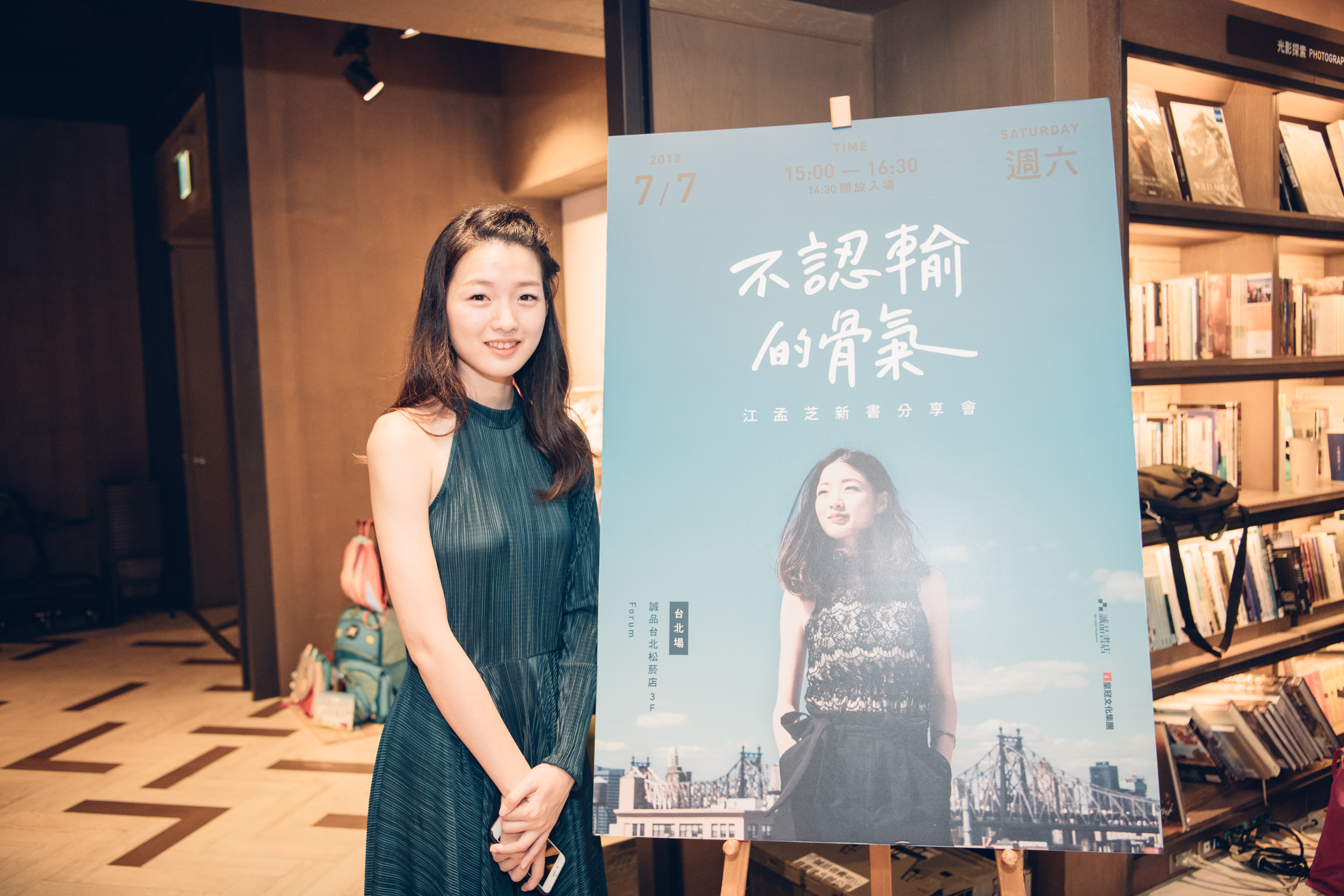 MengChih standing in front of a poster of her book cover in a bookstore.