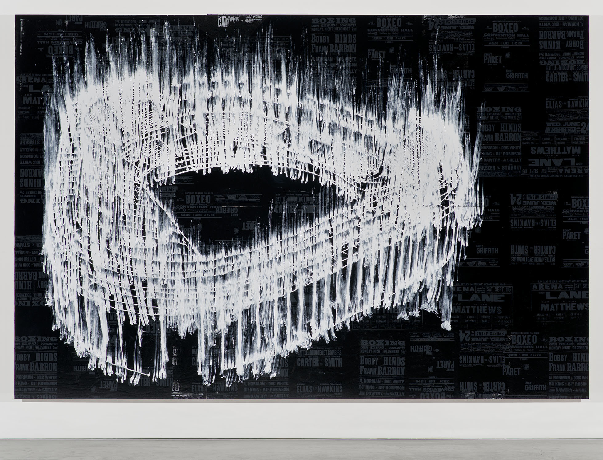 """<p """"="""""""">A large monochrome painting of a stadium, done on a collage of dark-hued reproductions of boxing posters."""