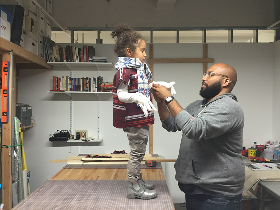 A father dressing his child standing on the table