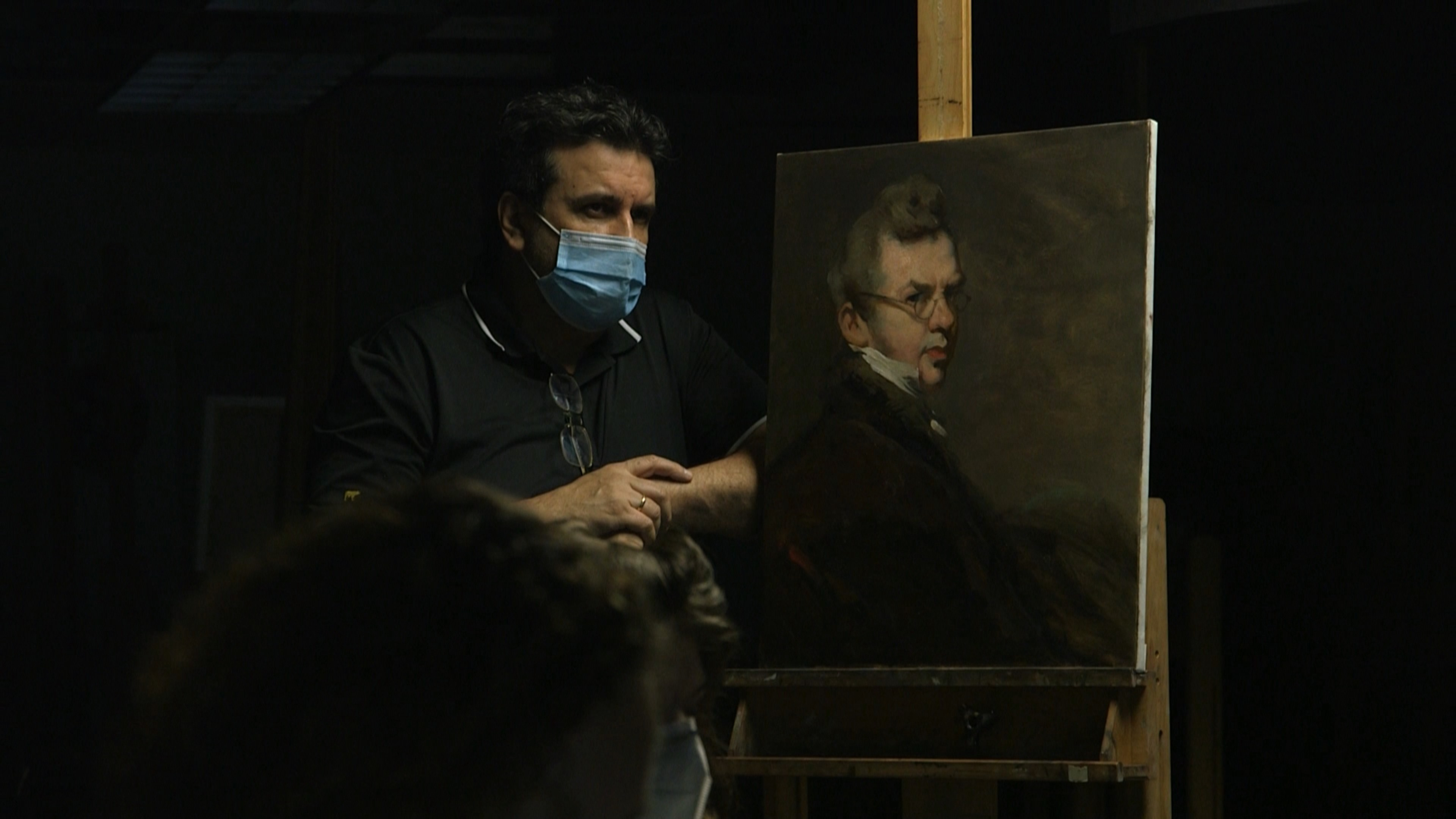 In a dark room, the light highlights a man in a medical face mask with his arm pressing against a classical style portrait painting of a man.