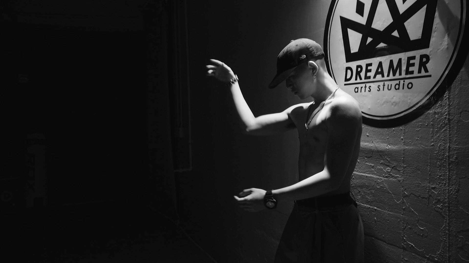 A high contrast B&W image of a young man making a graceful dancer's pose with his arms. He is shirtless and stands in front of a round sign reading Dreamer Art Studio.