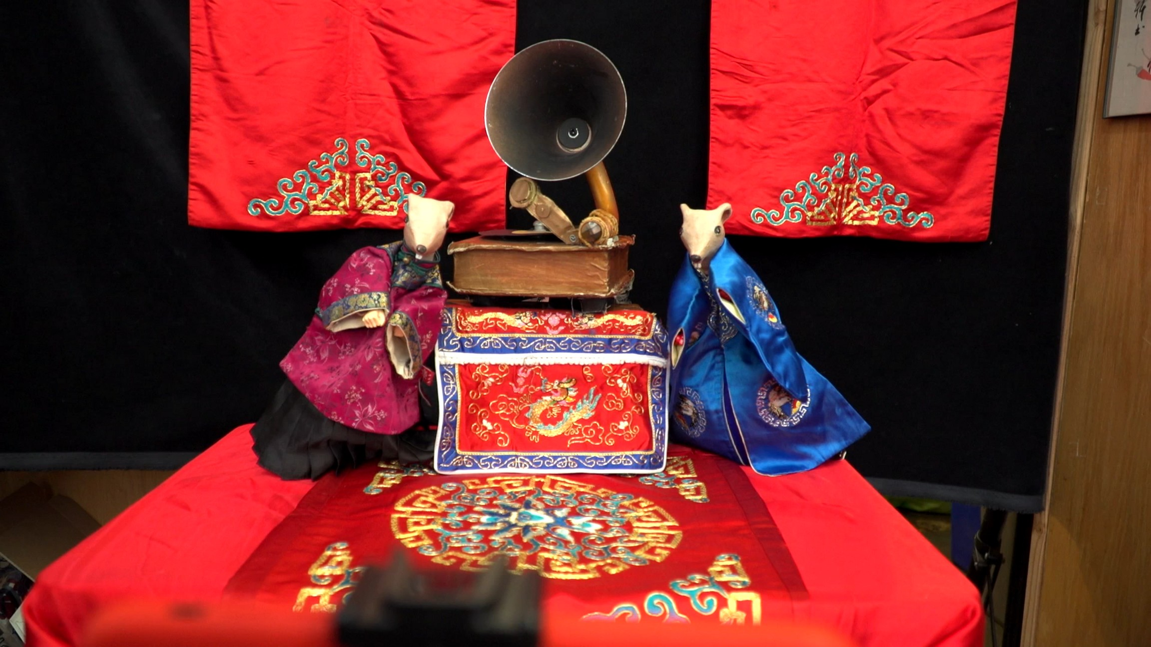 Two mouse-shaped puppets wearing traditional Chinese robes, one purple, one blue, rest against a model gramophone. They are on a stage draped with embroidered red silk.